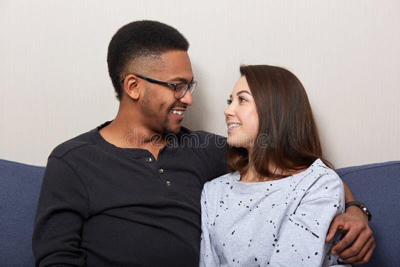 愉快的夫妇照片在微笑对彼此的爱看起来的,在家是,一起花费时间,观看影片,当坐沙发时 免版税库存照片