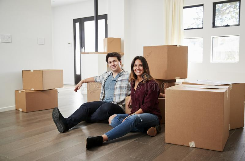 愉快的夫妇画象坐箱子围拢的地板在新的家在移动的天 库存图片