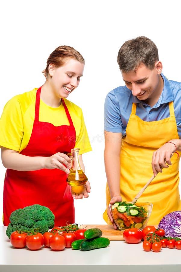 愉快的夫妇画象,当烹调在白色时的菜沙拉 免版税库存图片