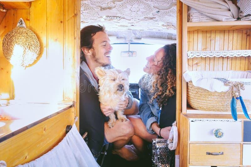 愉快的夫妇获得乐趣在有他们的狗的在旅行期间-一起享受时间的年轻人葡萄酒微型货车 免版税图库摄影