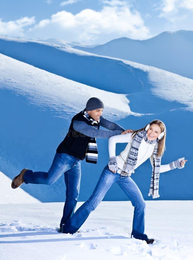 愉快的夫妇获得乐趣在雪 免版税库存照片