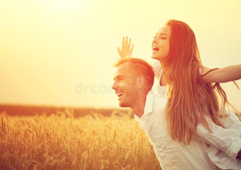 愉快的夫妇获得乐趣户外在麦田 免版税库存图片