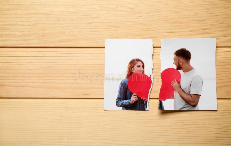 愉快的夫妇被撕毁的照片在木背景的 离婚的概念 库存照片