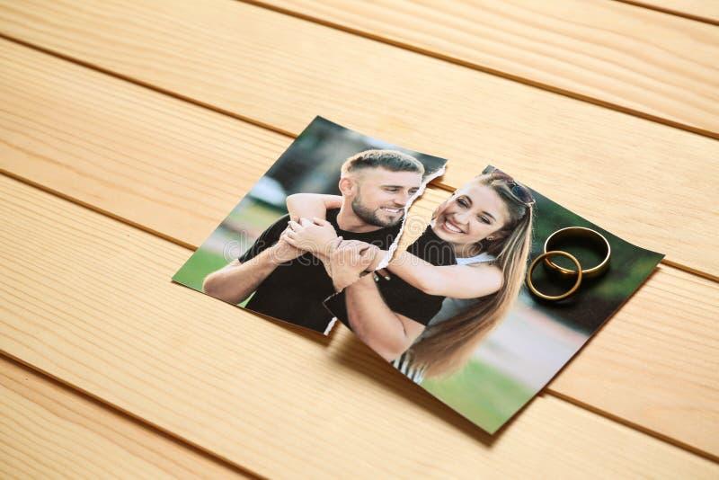 愉快的夫妇被撕毁的照片在木背景的 离婚的概念 免版税库存照片