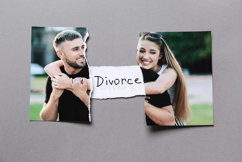 愉快的夫妇被撕毁的照片在灰色背景的 离婚的概念 免版税库存图片