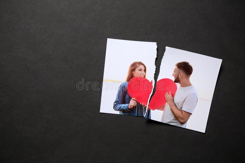 愉快的夫妇被撕毁的照片在黑暗的背景的 离婚的概念 库存照片