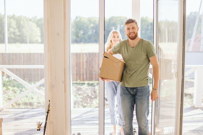 愉快的夫妇运载的纸板箱到新的家里在移动的天 免版税图库摄影