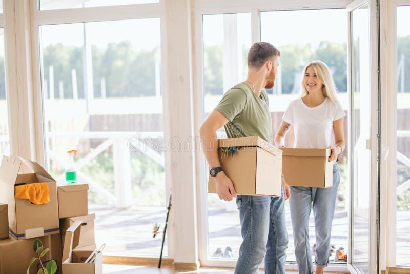 愉快的夫妇运载的纸板箱到新的家里在移动的天 免版税库存图片