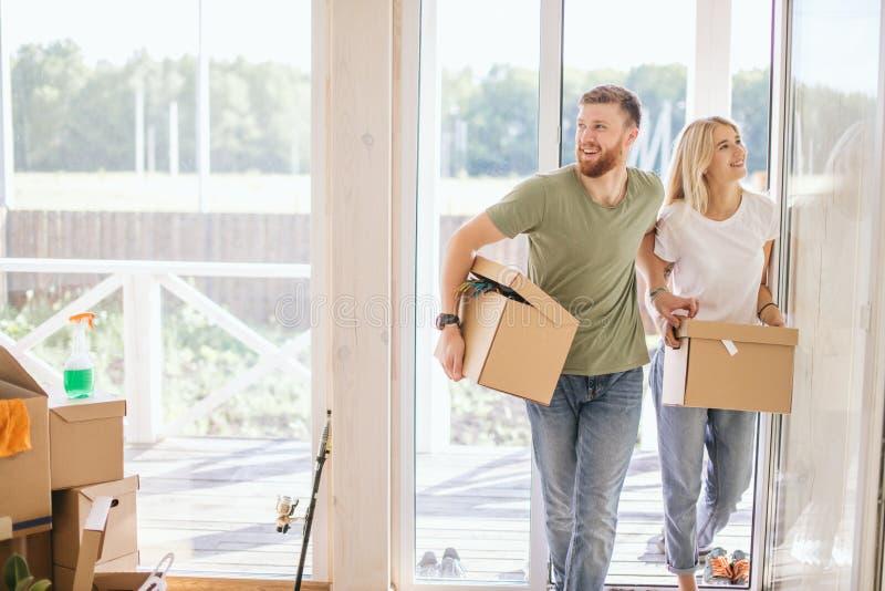 愉快的夫妇运载的纸板箱到新的家里在移动的天 库存照片
