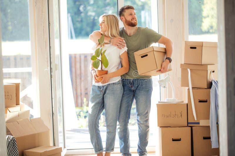 愉快的夫妇运载的纸板箱到新的家里在移动的天 库存图片