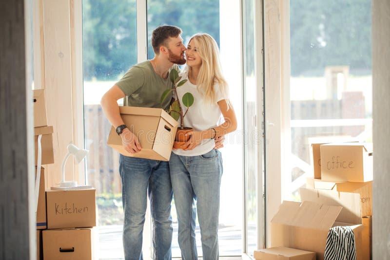 愉快的夫妇运载的纸板箱到新的家里在移动的天 免版税库存照片