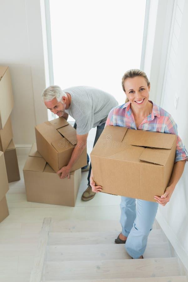 愉快的夫妇运载的纸板移动的箱子 图库摄影
