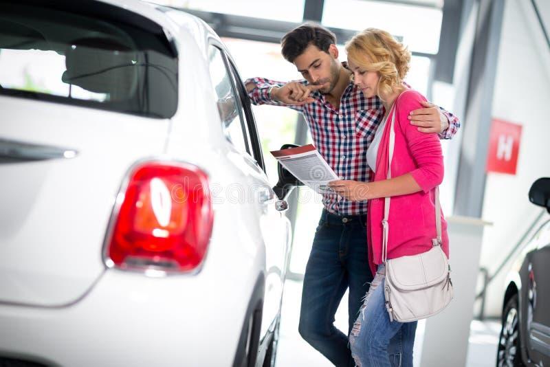 愉快的夫妇选择买汽车 免版税库存照片