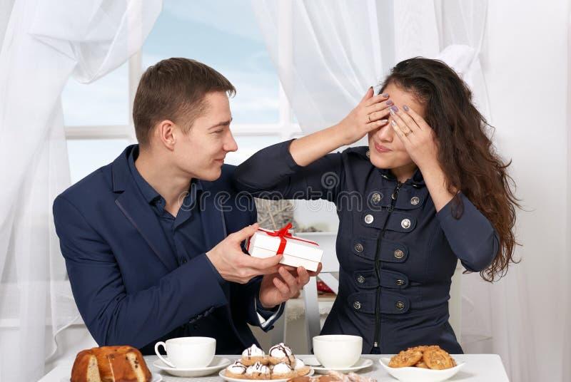 愉快的夫妇饮用的咖啡和有乐趣,在窗口附近给礼物有天空视图-爱和假日概念 免版税库存照片
