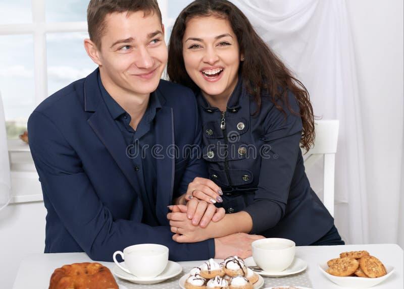 愉快的夫妇饮用的咖啡和有乐趣,窗口有在背景的天空视图-旅行并且爱概念 免版税库存照片