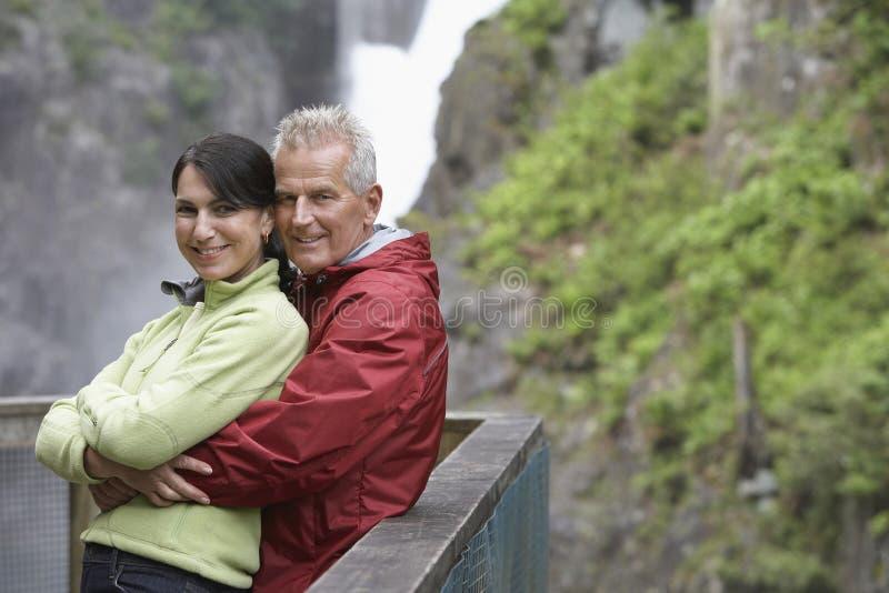 愉快的夫妇画象反对瀑布的 图库摄影