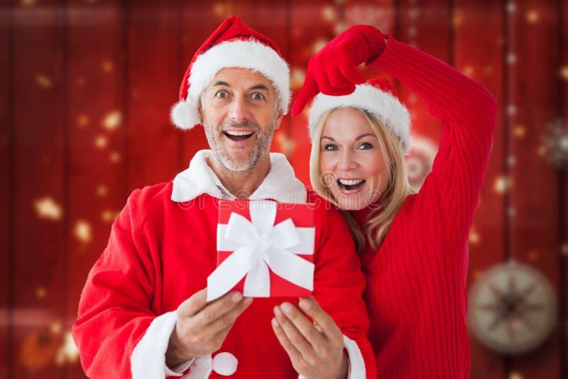 愉快的夫妇画象在圣诞老人的打扮拿着圣诞节礼物 免版税库存图片