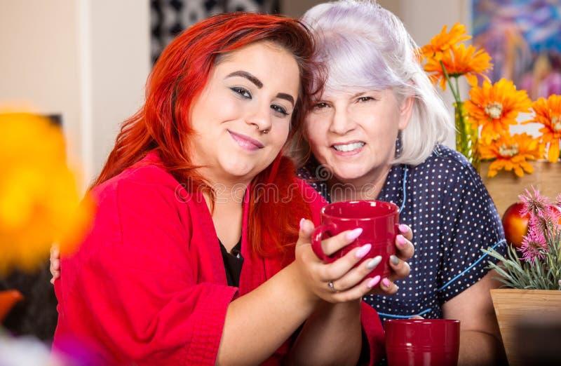 愉快的女儿和母亲用饮料 免版税库存图片