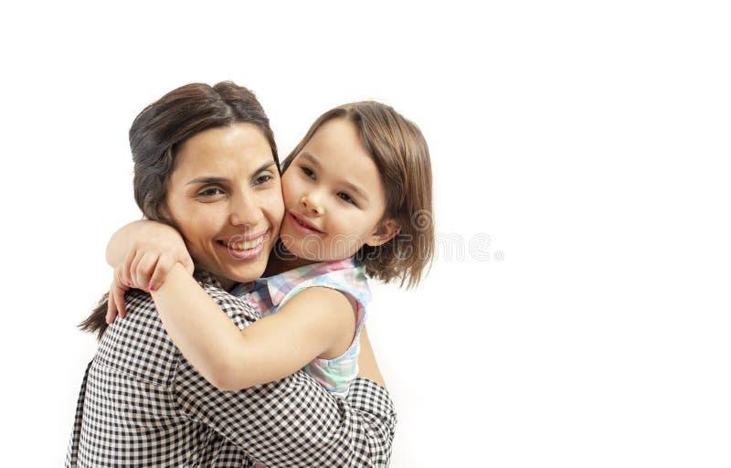 愉快的女儿拥抱她的母亲,隔绝在白色背景 库存照片