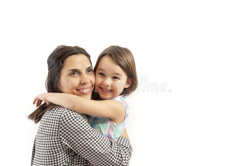 愉快的女儿画象拥抱她的母亲,隔绝在白色背景 库存图片