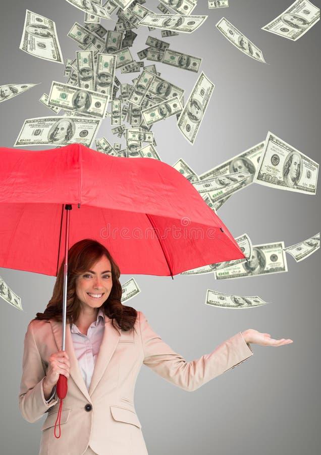 愉快的女商人在有金钱雨的伞下反对灰色背景 库存照片