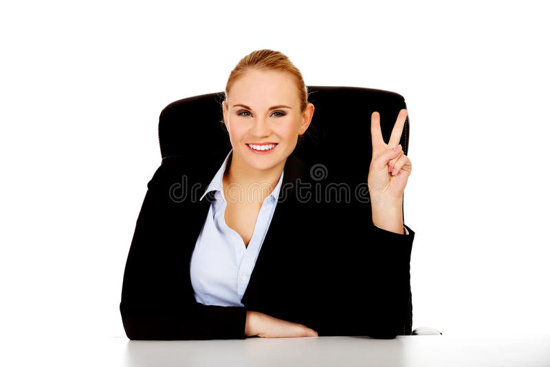 愉快的女商人坐在书桌后的和展示胜利签字 库存图片