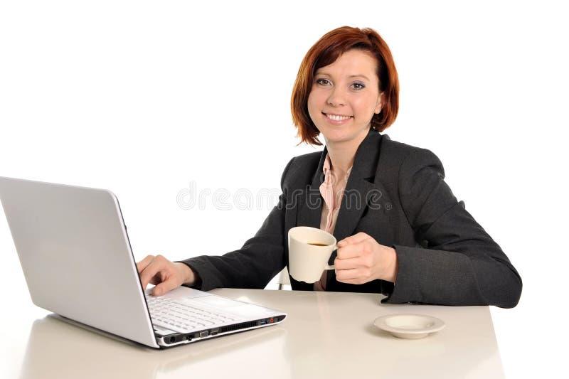 愉快的女商人用红色头发饮用的咖啡和微笑 免版税图库摄影