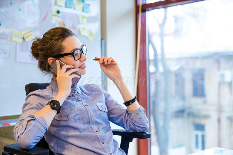 愉快的女商人谈话在手机在办公室 免版税库存图片