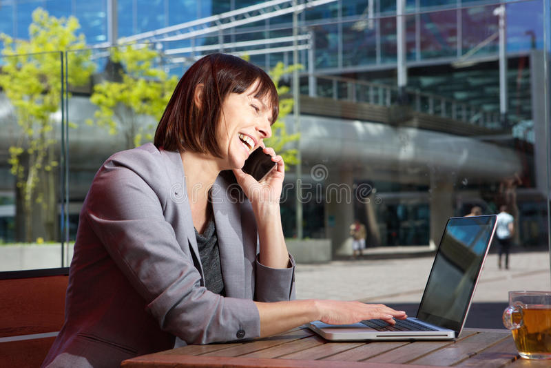 愉快的女商人谈话在手机,当研究膝上型计算机时 免版税图库摄影