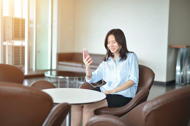 愉快的女商人谈话在电话在客厅 免版税库存图片