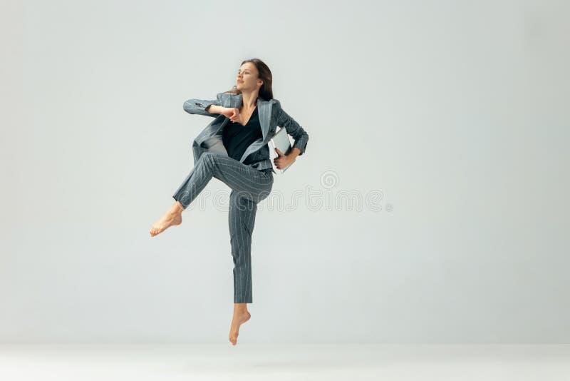 愉快的女商人跳舞和微笑被隔绝在白色 免版税图库摄影