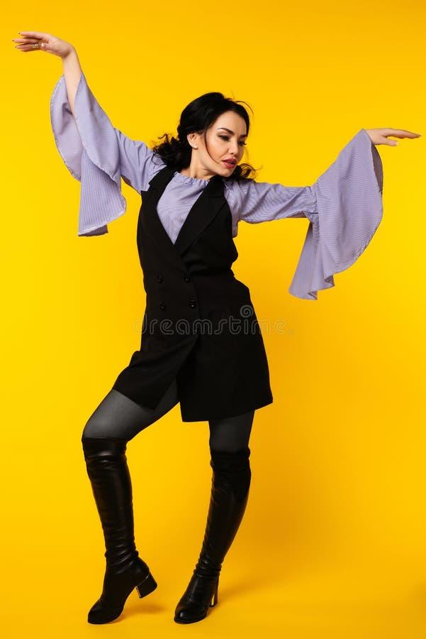 愉快的女商人跳舞,在黄色的全长画象 免版税库存图片