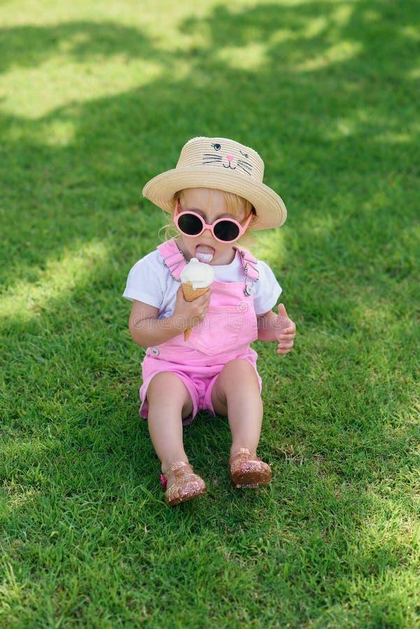 愉快的女婴穿戴了桃红色夏天衣裳,黄色帽子和桃红色太阳镜坐绿色草坪并且吃白色冰 免版税库存照片