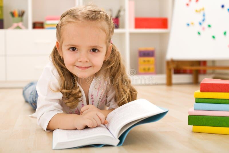 愉快的女孩一点实践的读取 免版税库存图片