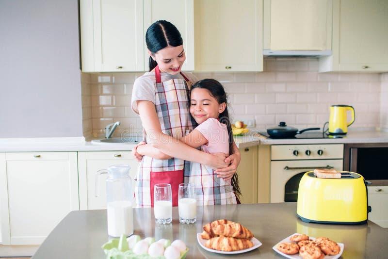 愉快的女孩一起站立在厨房和微笑 他们互相拥抱 妈妈看女儿 鲜美 免版税库存照片
