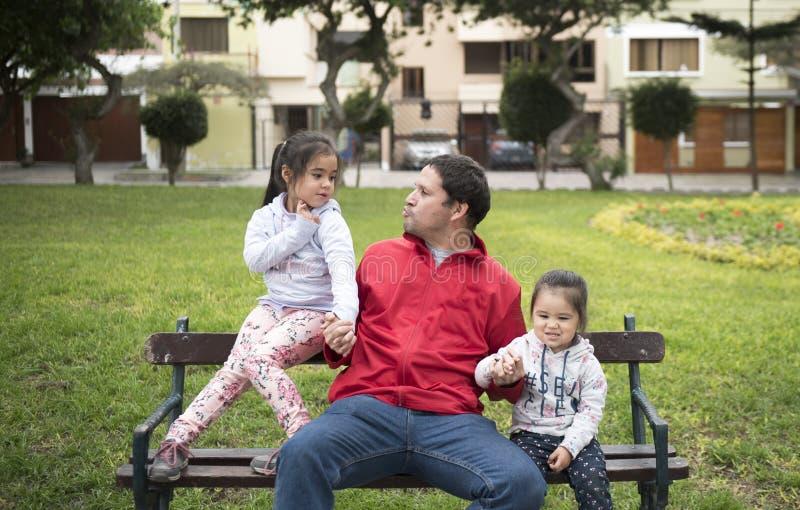 愉快的女孩享受好天气和阳光 互相和他们的父亲的美好的孩子放置和戏剧 免版税库存图片