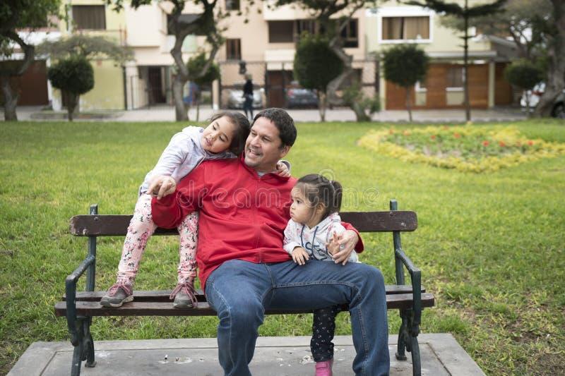 愉快的女孩享受好天气和阳光 互相和他们的父亲的美好的孩子放置和戏剧 免版税库存照片