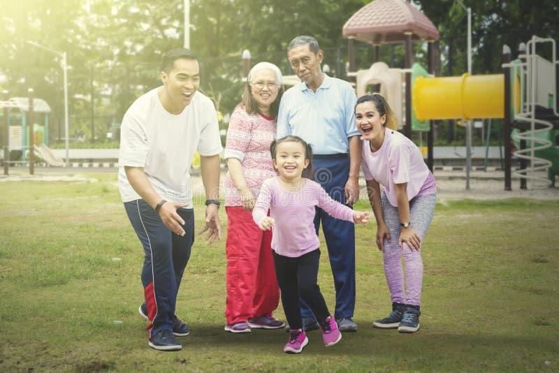 愉快的女孩使用与她的家庭在公园 免版税库存图片