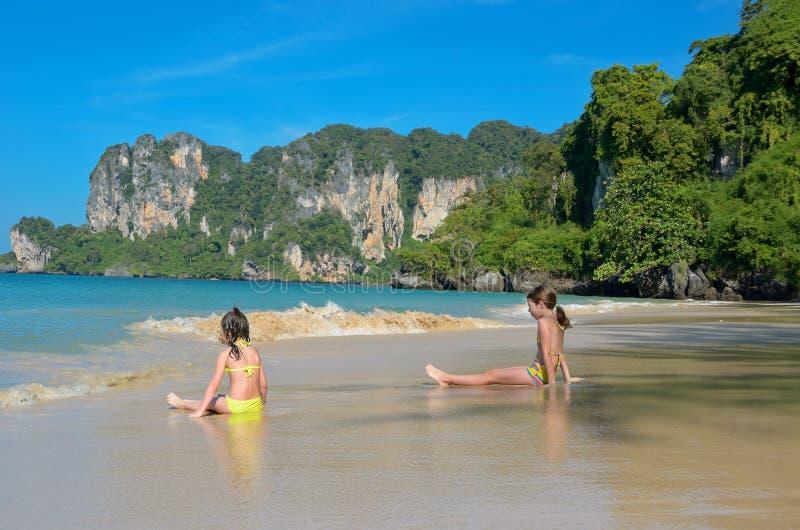 愉快的女孩充当热带海滩的海 免版税库存图片