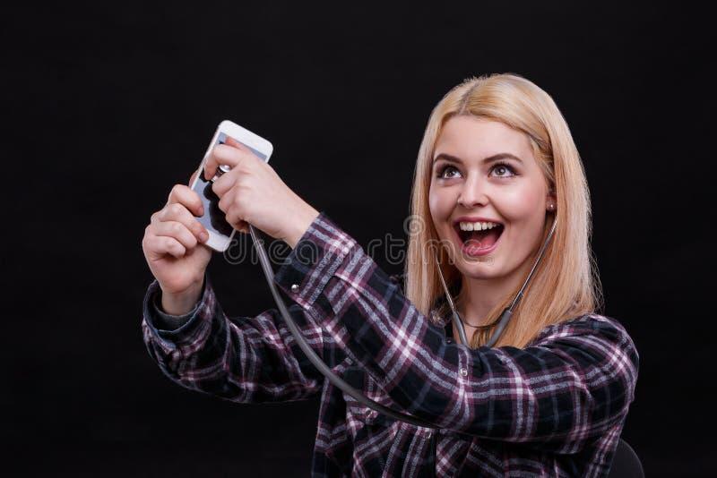 愉快的女孩听智能手机使用听诊器和笑 黑色背景 免版税库存照片