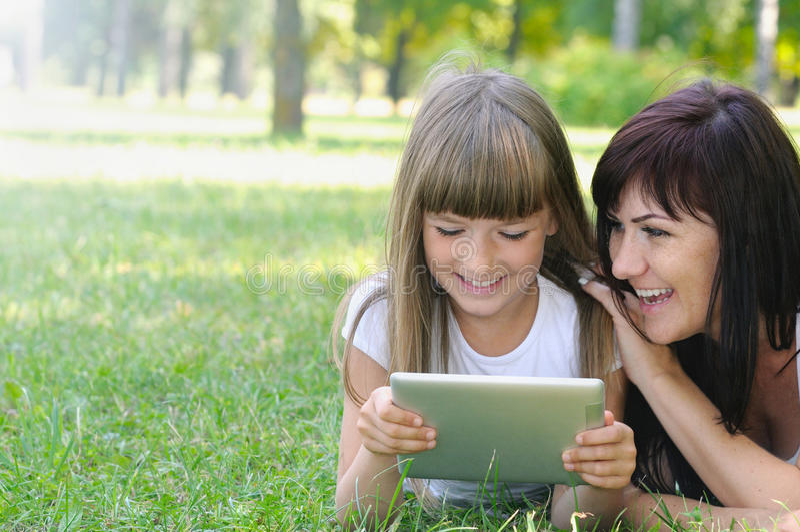 愉快的女孩和她的母亲获得在草的乐趣在公园 图库摄影