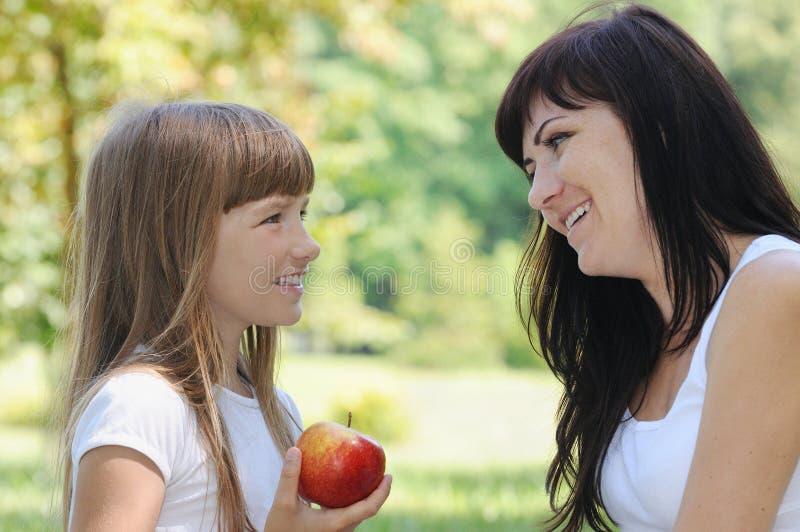 愉快的女孩和她的母亲获得在野餐的乐趣在公园在su 库存图片