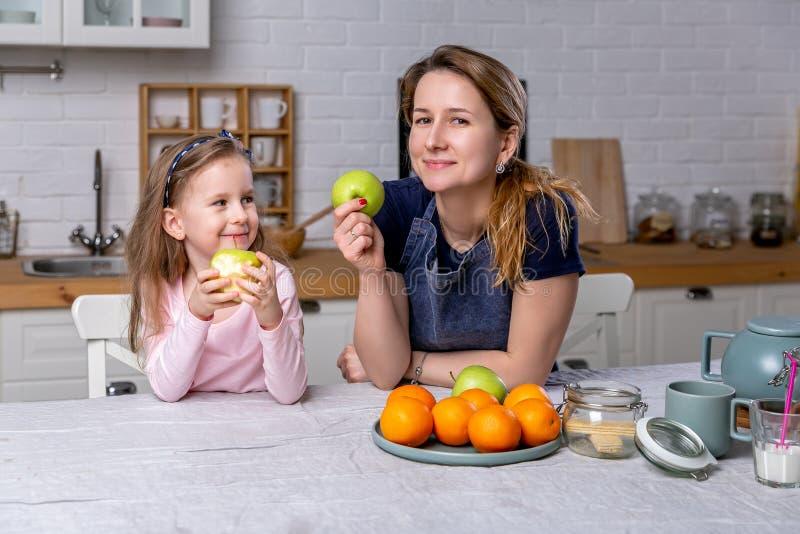 愉快的女孩和她美丽的年轻母亲一起食用早餐在一个白色厨房 他们获得乐趣并且吃着苹果 库存图片