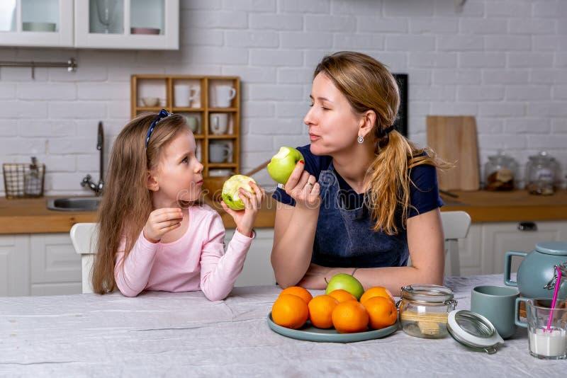 愉快的女孩和她美丽的年轻母亲一起食用早餐在一个白色厨房 他们获得乐趣并且吃着苹果 图库摄影