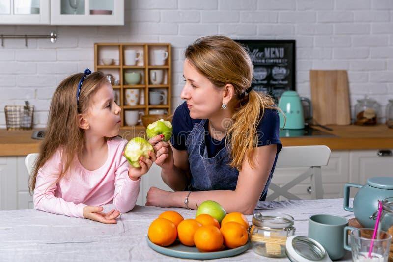 愉快的女孩和她美丽的年轻母亲一起食用早餐在一个白色厨房 他们获得乐趣并且吃着苹果 库存照片