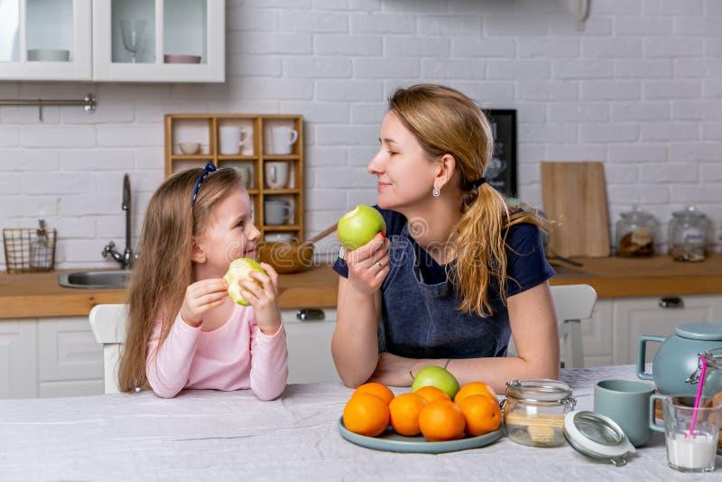 愉快的女孩和她美丽的年轻母亲一起食用早餐在一个白色厨房 他们获得乐趣并且吃着苹果 免版税库存图片