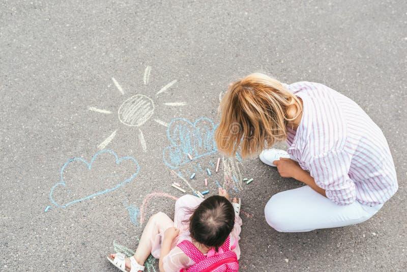愉快的女孩和母亲图画顶视图与白垩的在边路 与孩子学龄前儿童一起的白种人女性戏剧与 库存图片
