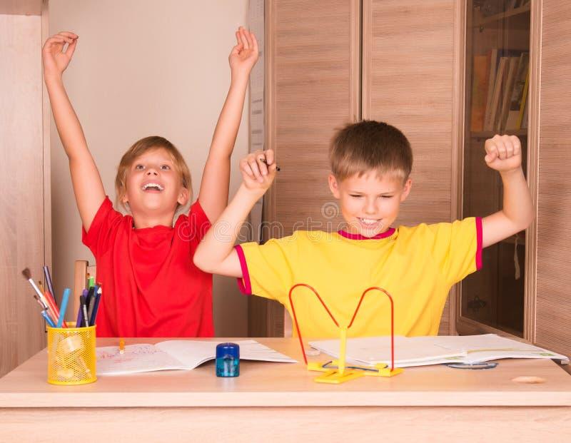 愉快的女孩和男孩画象准备好与他们的家庭作业 Childr 免版税库存图片