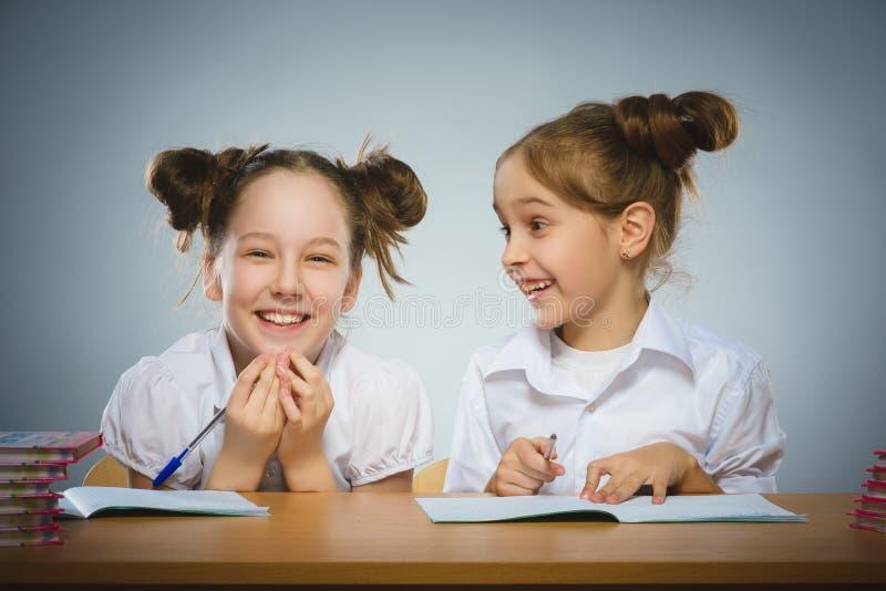 愉快的女孩在书桌坐灰色背景 背景黑名册概念copyspace学校 免版税库存照片