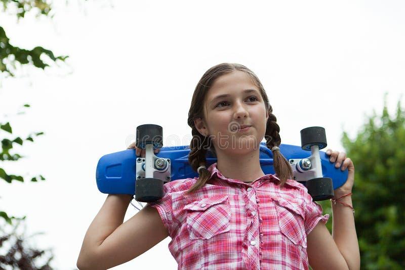 愉快的女孩在公园拿着在她的肩膀的一个蓝色滑板 免版税库存图片